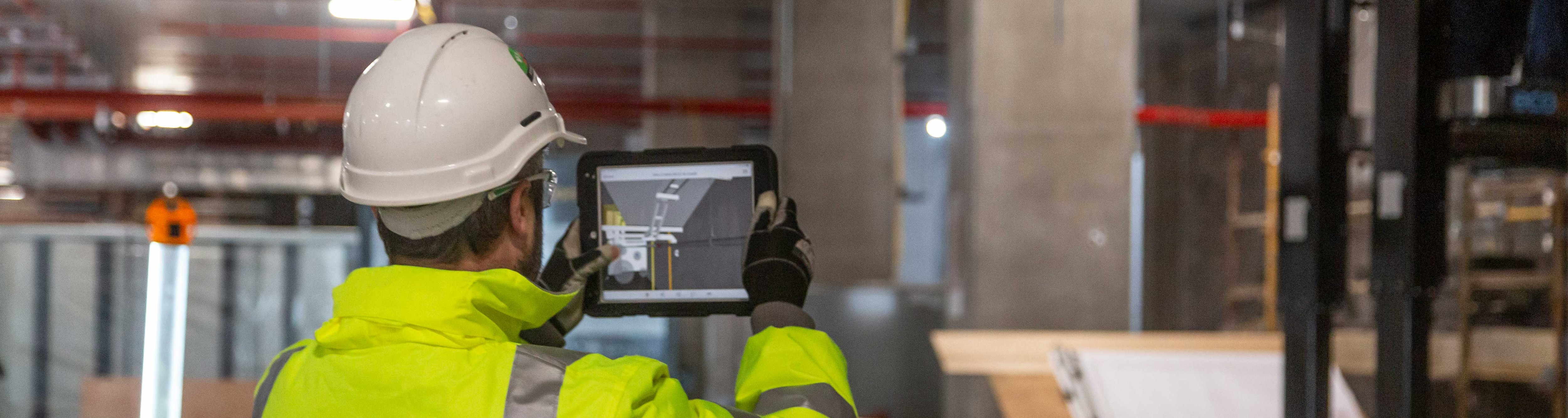 A man using a tablet device at construction site