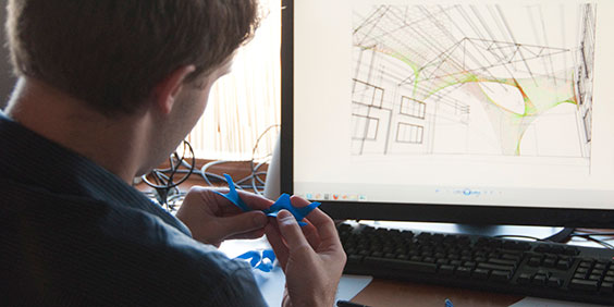 architect in front of computer with architectural model drawings
