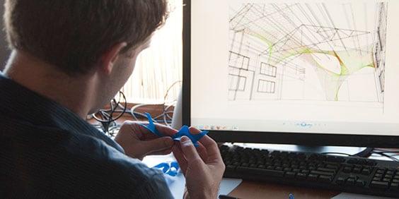 arquiteto na frente do computador com desenhos de modelo arquitetônico