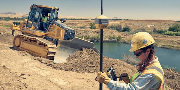 Trabalhadora em obra utilizando programa de levantamento topográfico