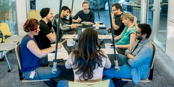 現代的なオフィスの中、テーブルを囲んでいる人々