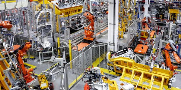 oThis image shows robotic arms being used in a car manufacturing plant.