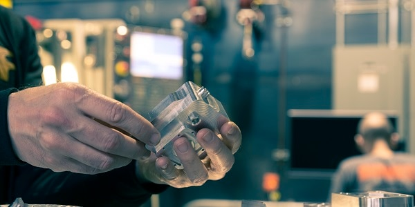 The image shows a man working on a 3D printed metal part  at Autodesk Pier 9 Workshop in San Francisco