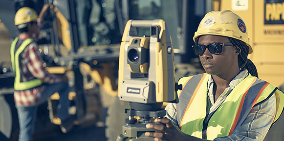 Construction workers using scanning and measuring devices at a construction site.