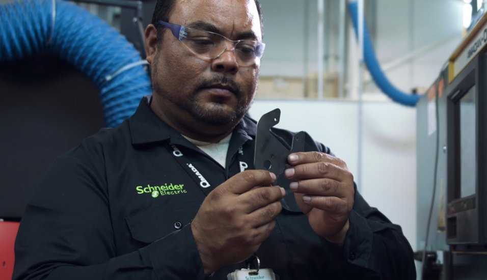 Image showing Schneider Electric employee inspecting injection molded plastic part