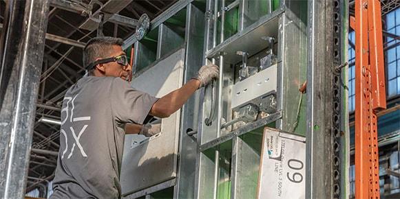 Man i skyddsglasögon bygger ett modulsjukhus