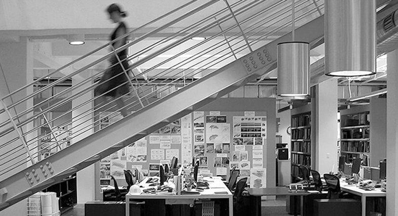 Foto i gråskala från ett kontor med en kvinna som går nedför en trappa