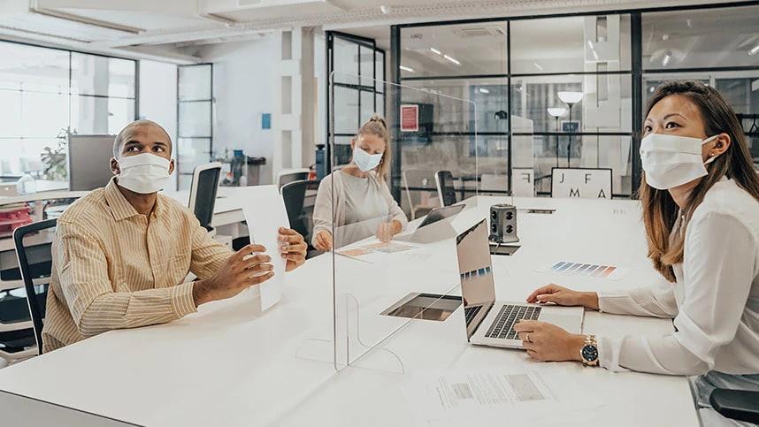 En man och en kvinna med munskydd sitter vid ett konferensbord och jobbar