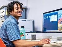 Ung leende man klädd i en blå tröja framför en bärbar dator