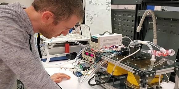 Man in a gray hoodie looking at a ventilator prototype