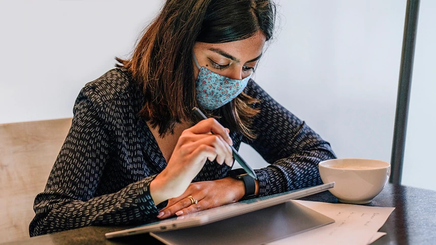 Kvinna med munskydd som arbetar vid en surfplatta