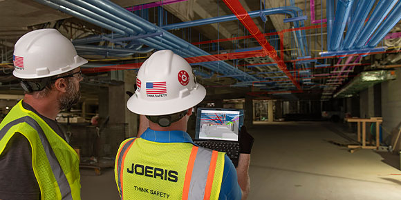 Two people inside a construction site wearing safety gear and using construction software on a tablet