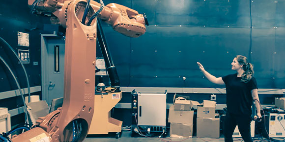 A woman in a robotics lab working in motion with a large orange robot