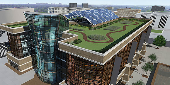 A 2D glass building with a green landscaped rooftop with pathways and solar panels