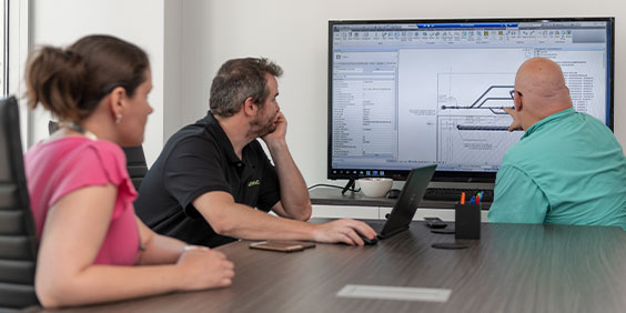 会議室の大画面で設計を見る男性 2 人と女性 1 人