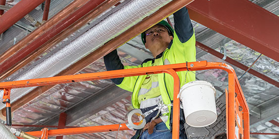 Um funcionário de construção em um elevador de plataforma hidráulica, trabalhando em um conjunto de tubulações de construção