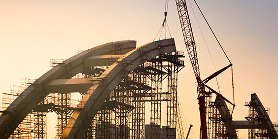 A half-built concrete arc supported by scaffolding with a crane in the background