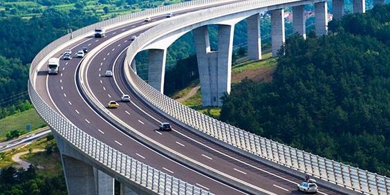 Изогнутая автомагистраль, по которой едут легковые автомобили, окруженная холмами и деревьями