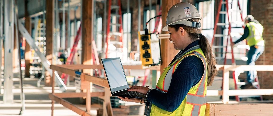 Bouwvakker die op een bouwplaats een laptop gebruikt