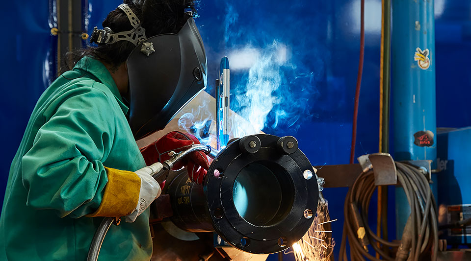 Woman wearing protective welders mask and equipment fabricating a piece of metal piping with sparks flying