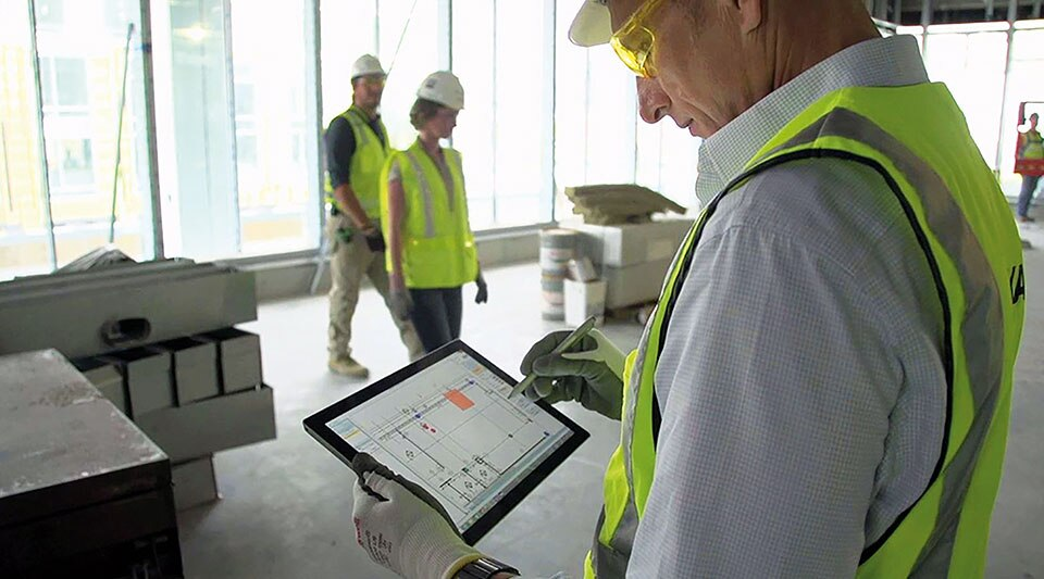 Construction site with man in the foreground using a tablet to review floor plans