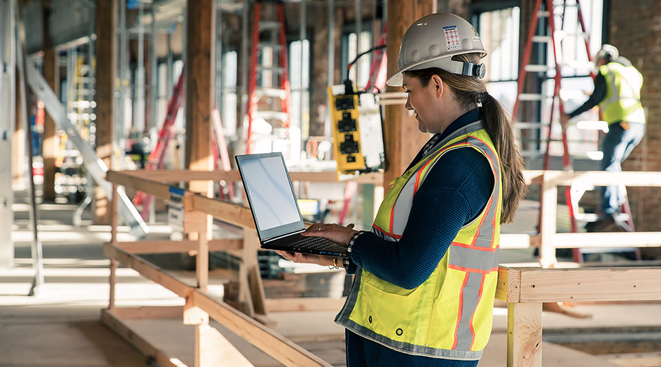 BIM professional from Fortis Construction on a construction site looking at laptop