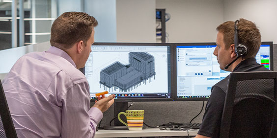 2 名男子坐在 2 台電腦螢幕前,其中 1 台畫面顯示黑白建築模型