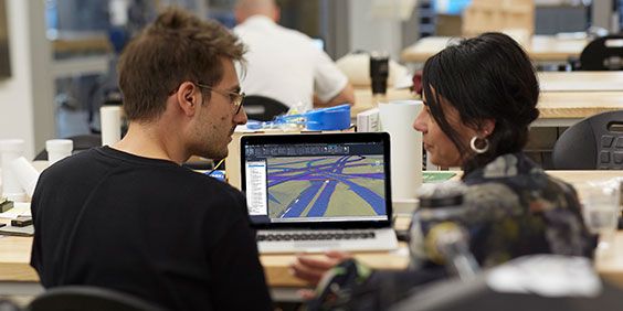 A man and a woman in an office talk while viewing a model of a highway on laptop