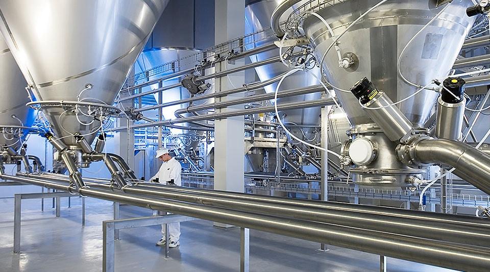 En mand, der arbejder med et stort industrielt forarbejdningssystem, der består af metalventiler og rør