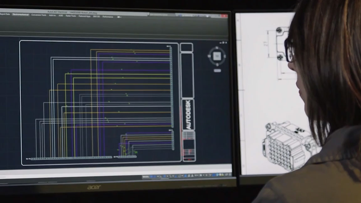 A woman working with AutoCAD software on two monitor screens