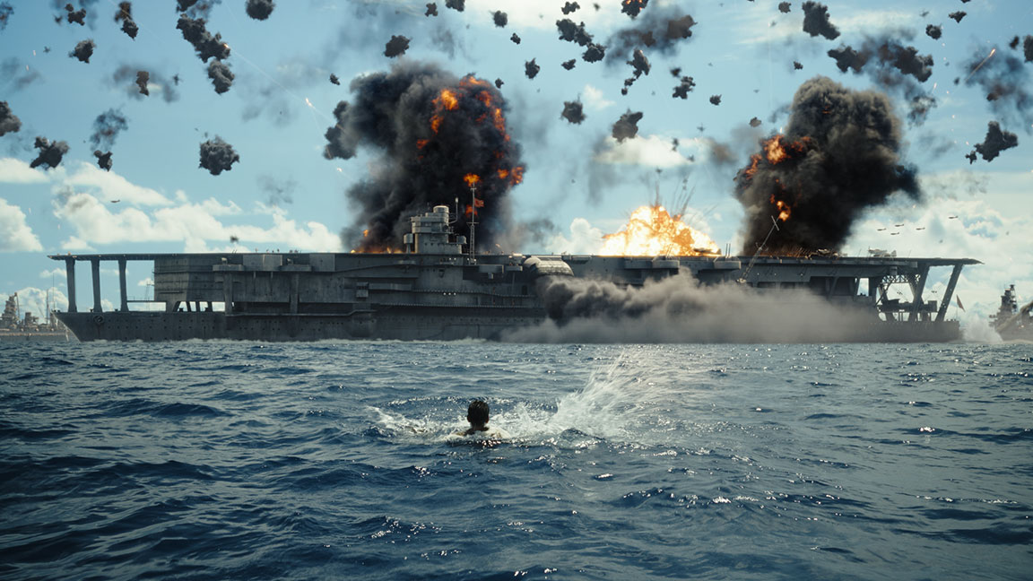 Image from Midway film of an aircraft carrier in the ocean with bombs exploding into fire and smoke and a man in the water