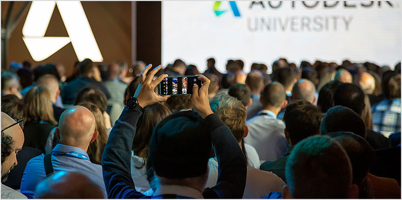 An Autodesk University attendee takes a photograph among a large crowd of people
