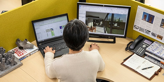 Woman at a desktop sitting in front of a laptop and monitor