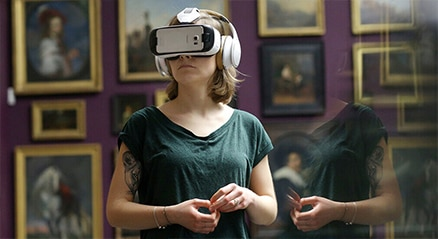 Reflection of a woman looking into a mirror wearing virtual reality goggles with paintings in the background