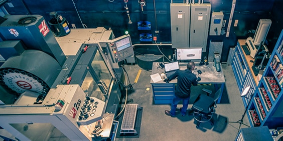 Aerial view of man standing at workbench viewing a computer screen while surrounded by manufacturing machinery