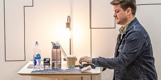 Man seated at table working on laptop next to coffee cup and water bottle