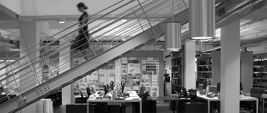 Grayscale photograph of an office with a woman walking down a flight of stairs