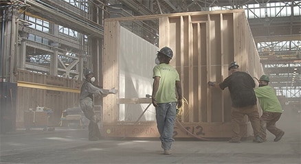 Four men working on a modular building in a dusty construction facility