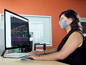 Kvinne ved et skrivebord sitter foran en laptop og en skjerm