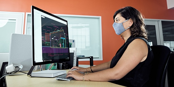 Woman wearing a mask seated at a desk working on a desktop