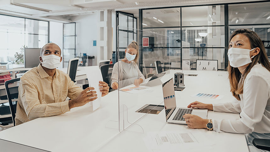A man and two women wearing face coverings while working at an office conference table
