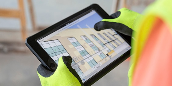Two hands holding a tablet device displaying Autodesk software