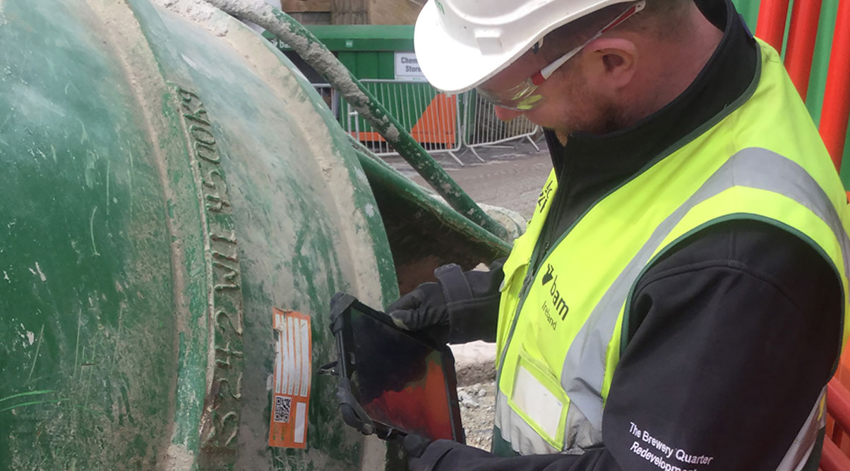 Construction worker scans a tag on a cement mixer