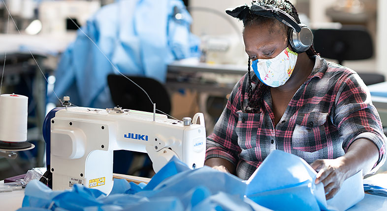 Worker sews personal protective equipment in ISAIC's apparel manufacturing facility
