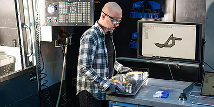 A mechanical engineer works with a large electronic tactile interface at work