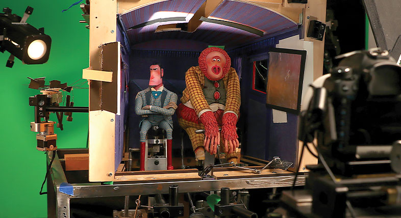 A motion studio set with a greenscreen, animated characters, props, and cameras