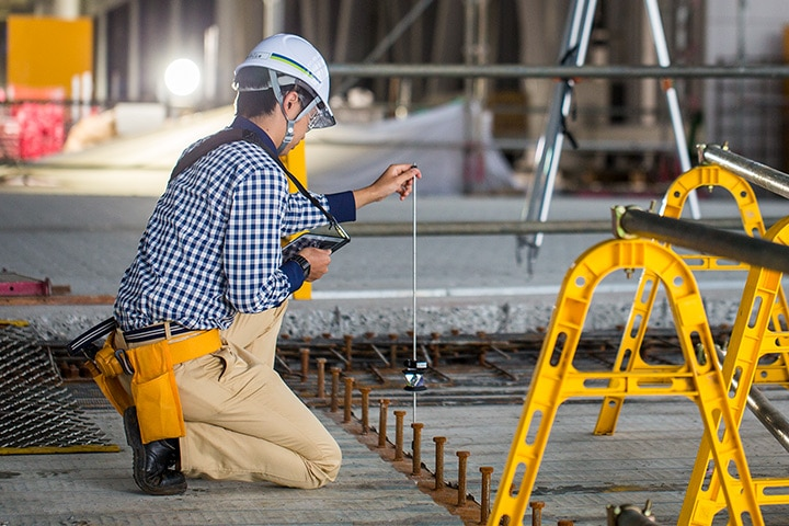Construction worker takes digital measurements on a construction site