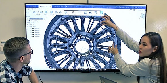 Man and woman looking at a design for a wheel on a large screen