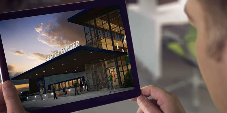 Man viewing a rendering of a health care center on a tablet