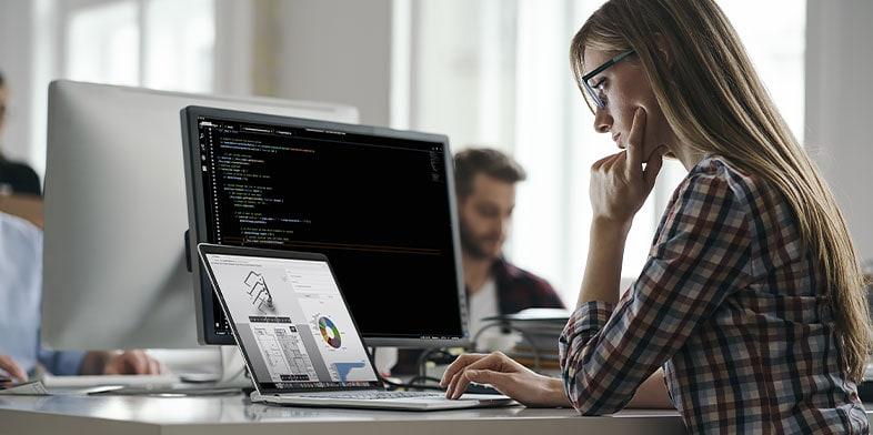 책상에 앉아 컴퓨터에서 Autodesk 소프트웨어로 작업 중인 여자.